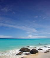 Strand Meer Steine im Wasser blauer Himmel blauer Ozean